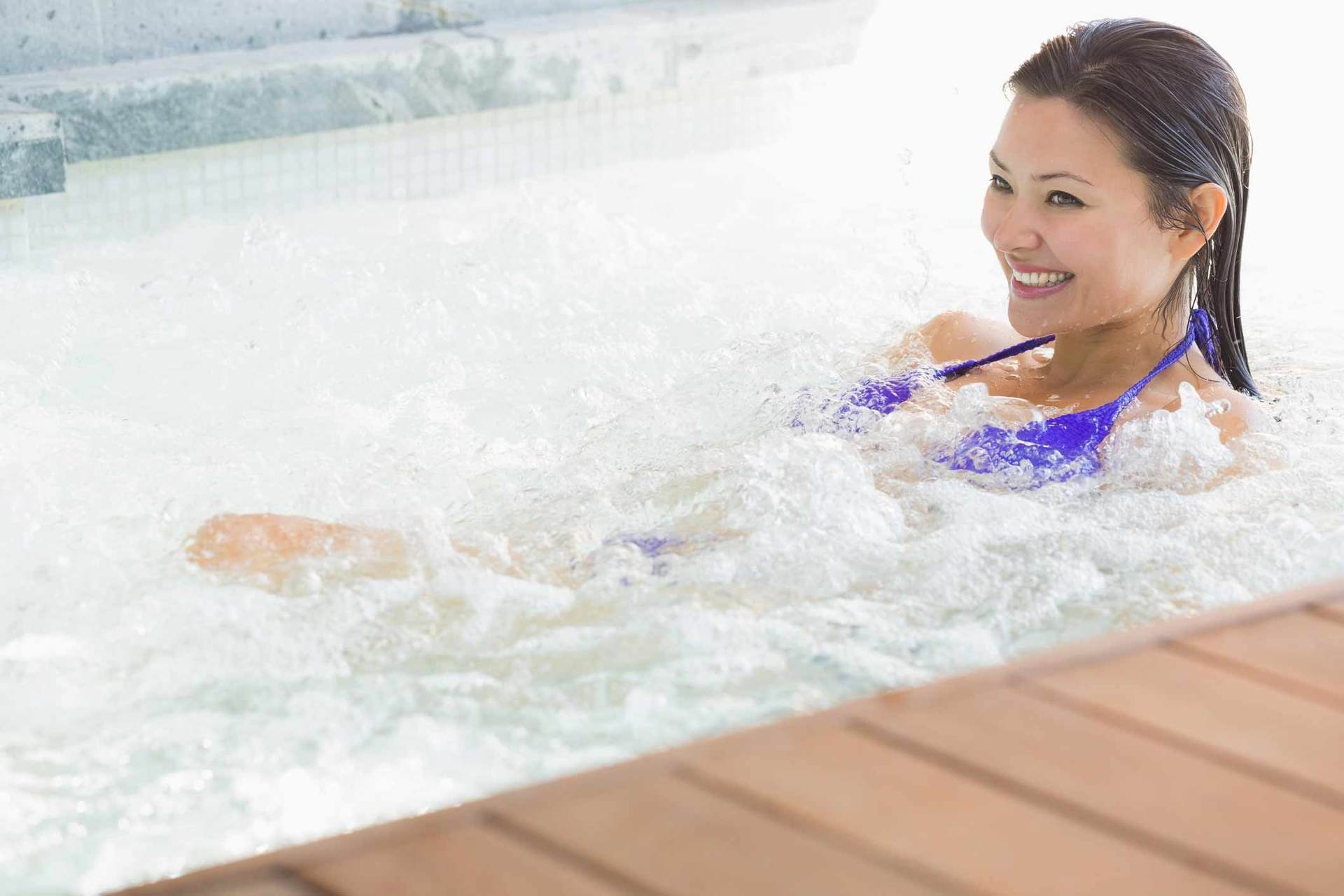 woman lounging in hot tub and smiling