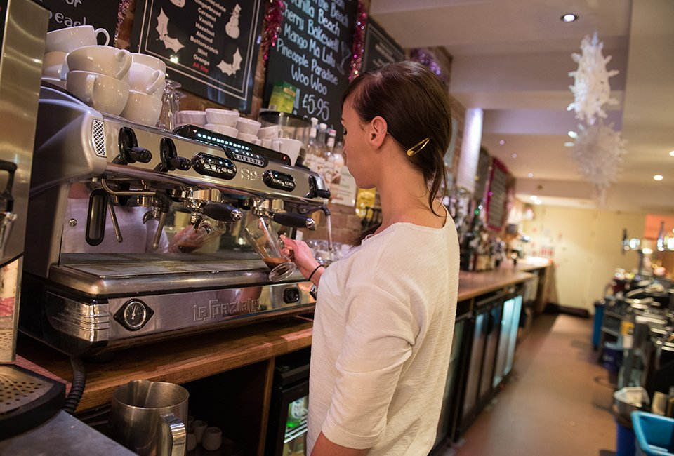 Employee at Enigma cafe making drink for customer