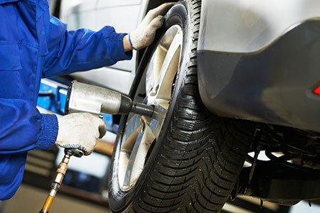 un meccanico mentre monta una gomma su una macchina