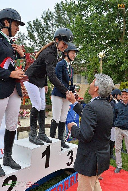 tre ragazze vestite in abbigliamento da equitazione e un uomo che le stringe la mano