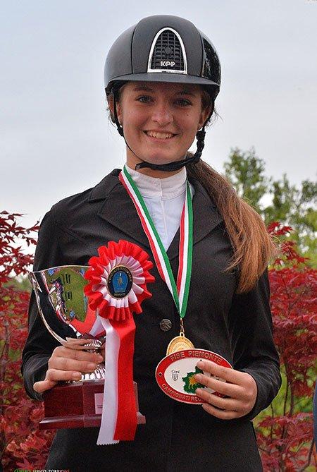 una ragazza vestita in abbigliamento da equitazione e con una medaglia una medaglia in mano