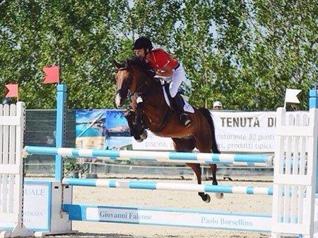 una ragazza su un cavallo mentre salta