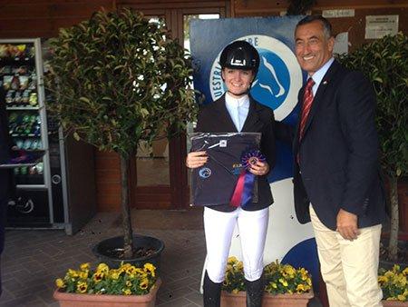 una bambina vestita in abbigliamento da equitazione e con una medaglia una medaglia in mano ad accanto un uomo