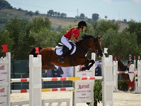 una ragazza durante l'equitazione salto ostacoli con un cavallo