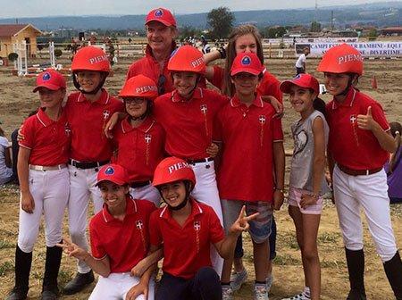 dei bambini vestiti in abbigliamento da equitazione