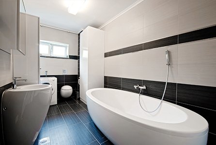 Bathroom with walls and floor tiled in black and white, and oval bath and washbasin