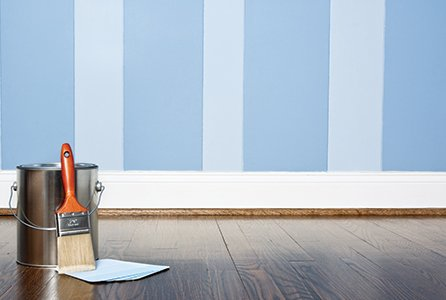 A paint pot and brush on a wooden floor in front of a wall painted in powder blue and sky blue stripes