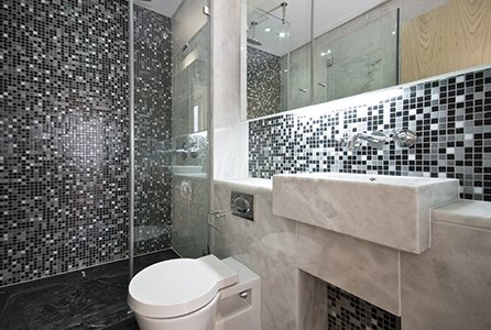 Black and white mosaic splashback tiling above a marble unit around a white toilet, beside a shower decorated with white sparkle pattern