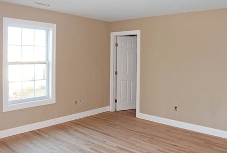 White window and door in an empty room with wooden floor, white skirtings and beige walls