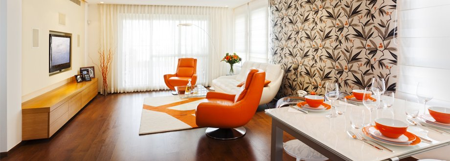A room decorated in white, with orange leather chairs facing a TV, orange crockery on a white table, and a large orange, khaki and black roller blind