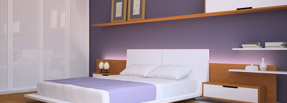 A bedroom with dark lilac walls picked up by a lighter lilac throw on a white platform bed, white wardrobes with glass doors, and bedside units in wood effect with white drawers