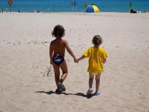 bambini si tengono per mano e vanno verso il mare