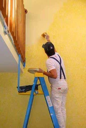 operaio mentre la pittura di parete in una casa