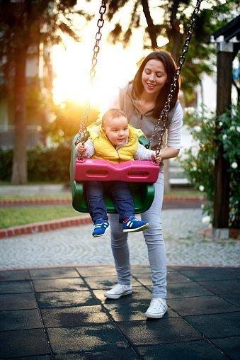 una donna mentre gioca con bambino su appesa amaca in un giardino
