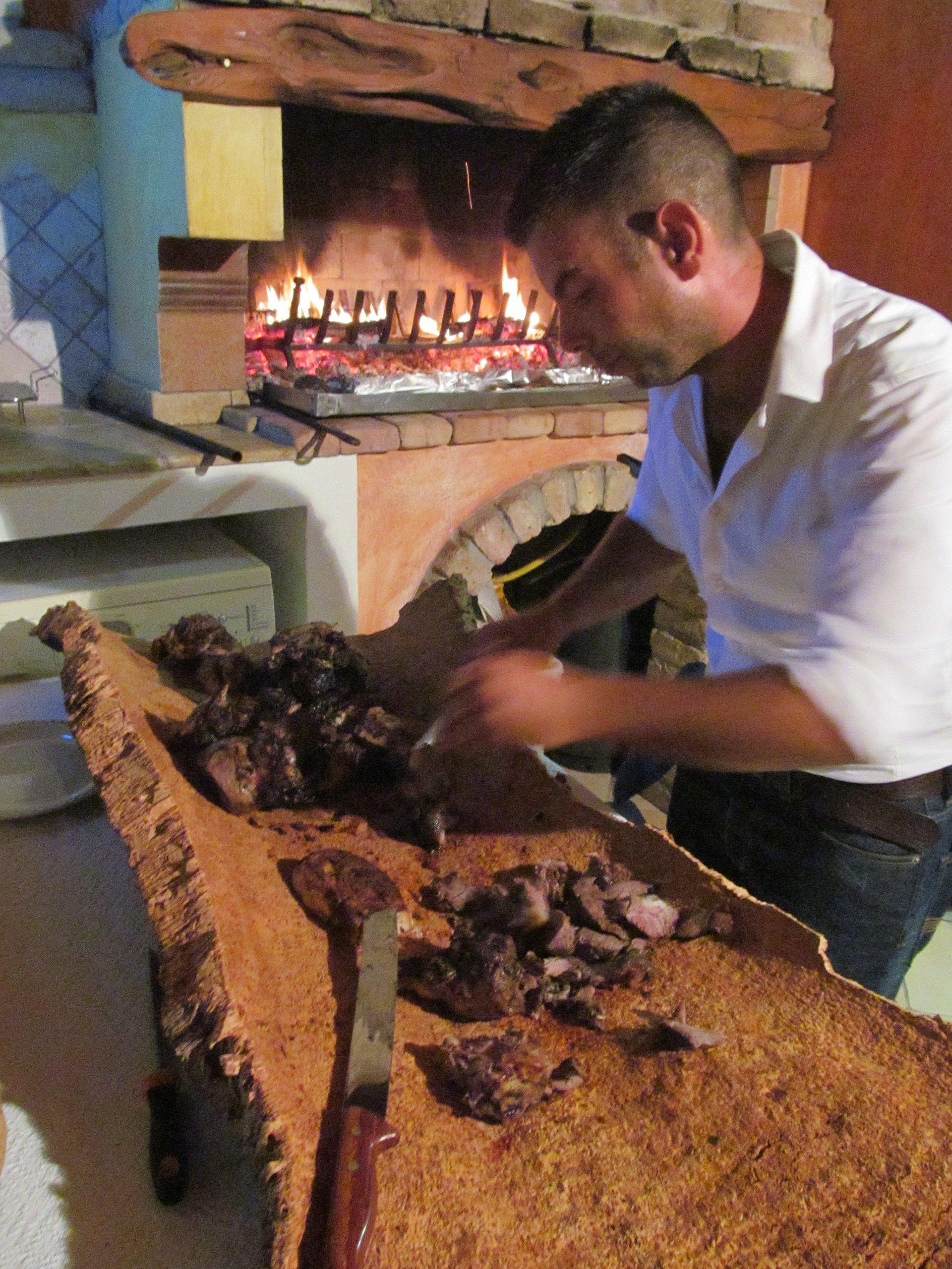 chef in una cucina mentre taglia carne