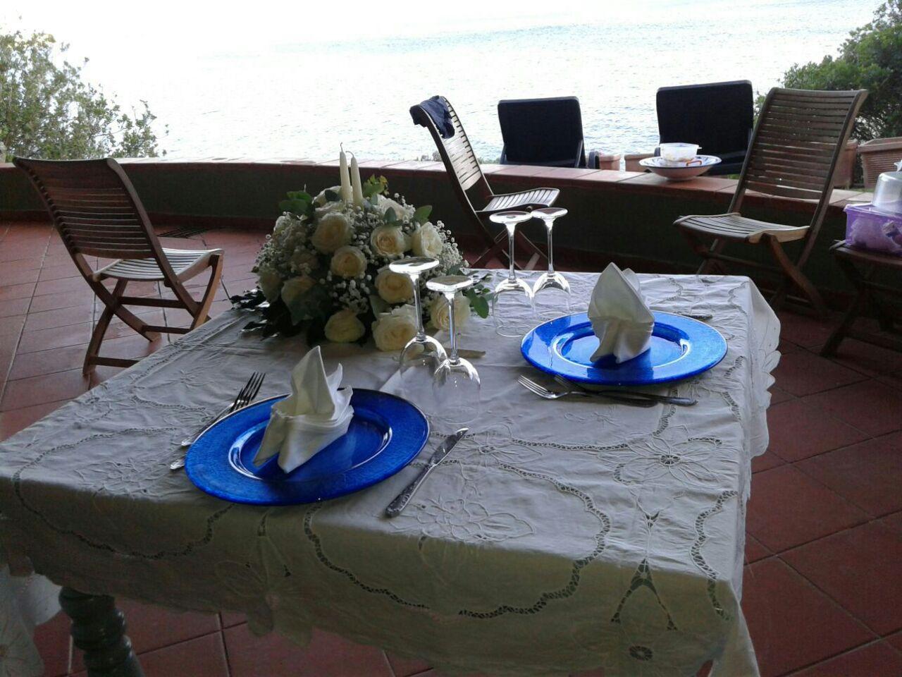 tavolo apparecchiato con un bouquet e due piatti-vista frontale