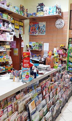 vista del bancone con sotto delle riviste e degli articoli da edicola e cartoleria