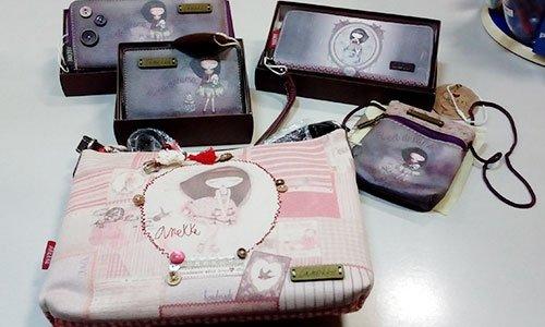 una borsetta rosa e bianca e portafogli e portamonete di color grigi e neri a sfumature con dei disegni