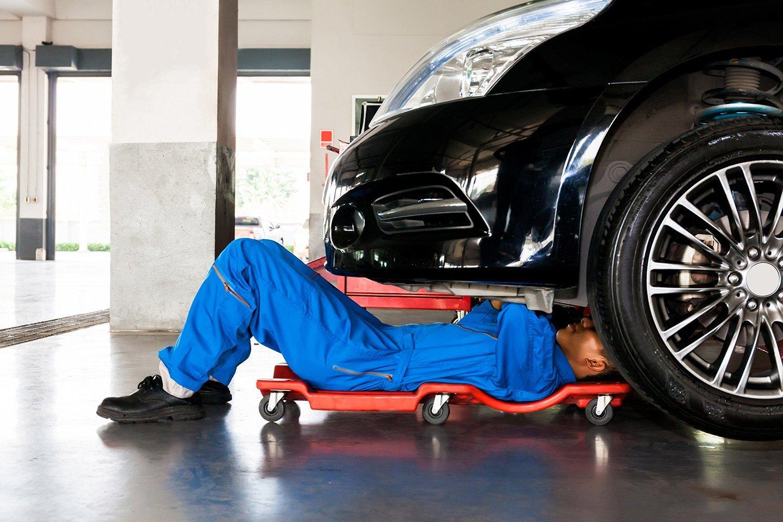 meccanico in tuta blu che ripara un auto sdraiato sul carrello