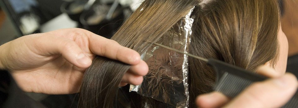 A stylist using a tail comb and foil to put highlights in a lady's hair