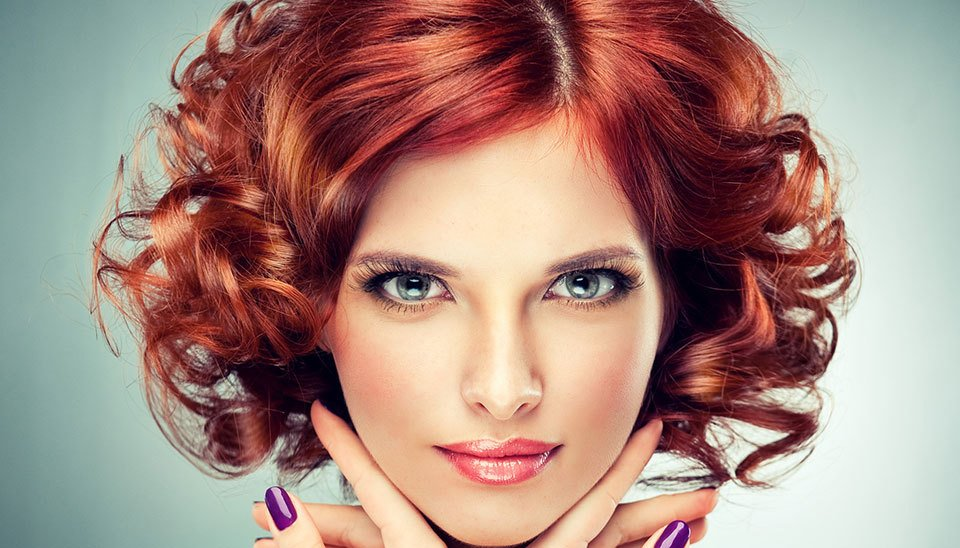 A lady with glossy red curly hair