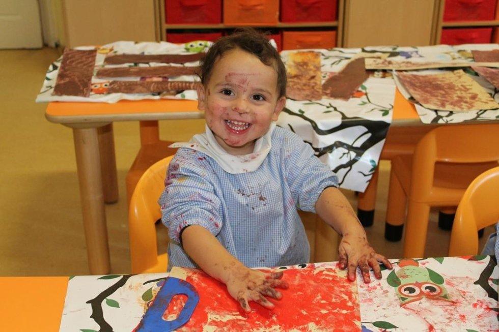 un bambino con le mani sporche di pittura