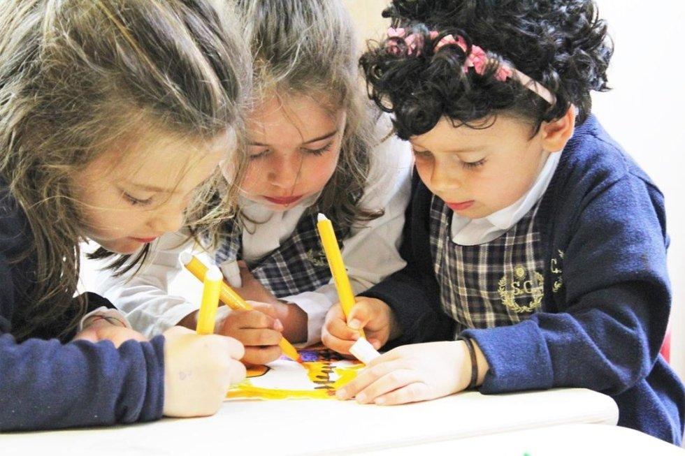 tre bambine intente a colorare