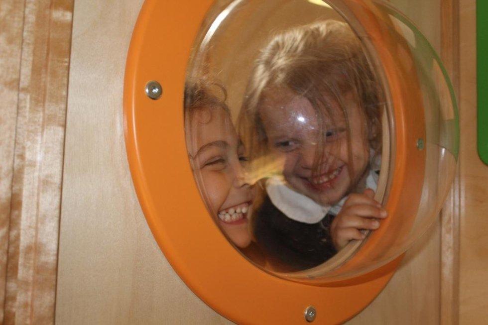 due bambini sorridono dietro a un oblò