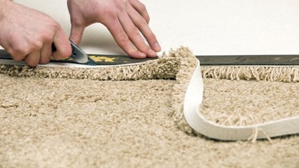A carpet fitter, cutting a rug to size
