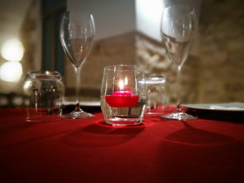Tavola con una candela, bicchieri e coppe