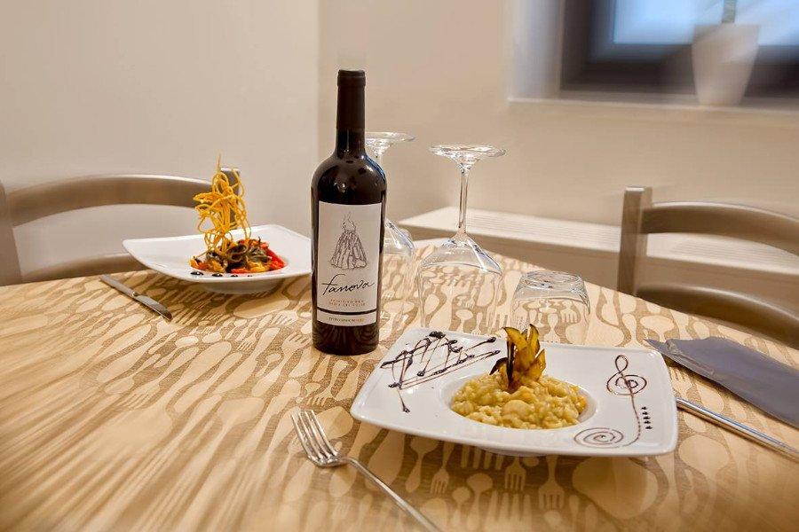 Tavola disposta, due piatti, due coppe e una bottiglia di vino