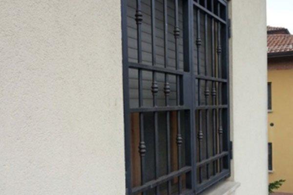 vista laterale di un' inferriata in ferro battuto e dietro una finestra