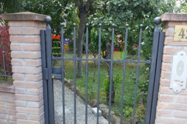 un cancello in ferro battuto grigio scuro e dietro la vista di un giardino