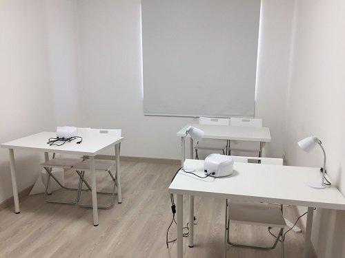 un'aula con tre scrivanie e delle sedie bianche