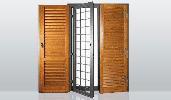due ante di due persiane in legno aperte e al centro una porta antintrusione in ferro