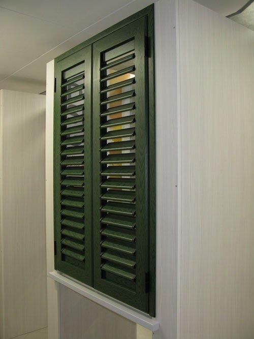 una persiana di color verde vista di lato