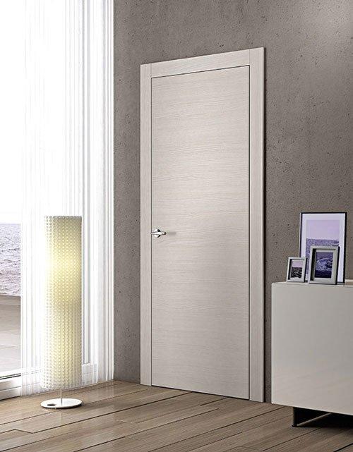 una porta beige chiara, sulla sinistra una lampada da terra e sulla destra un mobiletto con sopra delle cornici