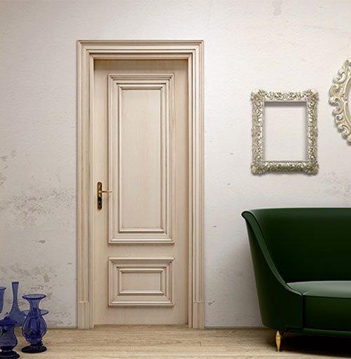 una porta color panna con maniglia dorata , sulla destra due specchi, uno quadrato e un o rotondo con ornamenti e sotto un divano in pelle verde