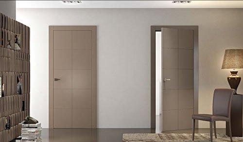 una stanza con una libreria beige sulla sinistra, sulla destra una sedia e un mobile con sopra una lampada e in centro due porte color beige chiaro