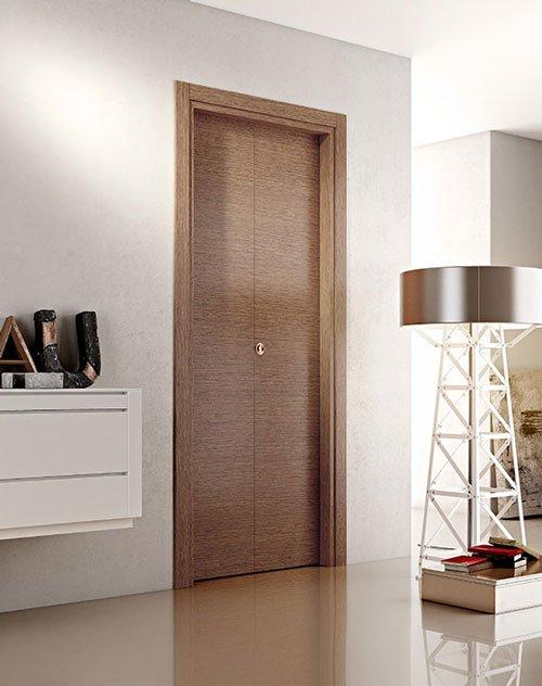 una porta in legno, sulla sinistra un mobile bianco a muro con sopra degli oggetti e sulla destra una lampada con un piedistallo a forma di traliccio