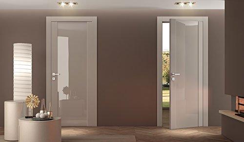 due porte color panna lucide e trasparenti e sulla sinistra una lampada da terra e un tavolino rotondo con sopra degli oggetti
