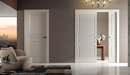 un salotto con una poltrona grigia e marrone sulla sinistra e al centro due porte in  legno color panna