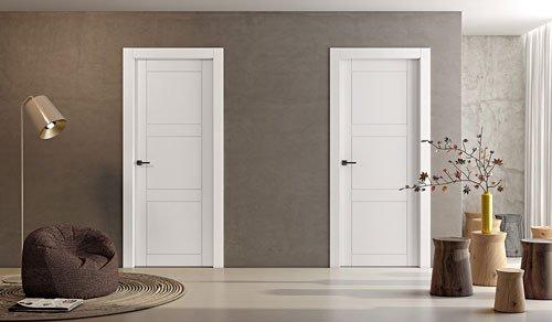 un salotto con un pouf marrone sulla sinistra, una lampada da terra, sulla destra degli sgabelli a forma di tronco con dei rami di una pianta e al centro due porte bianche