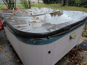 Broken Hot Tub Cover making a pool of rain water above the spa