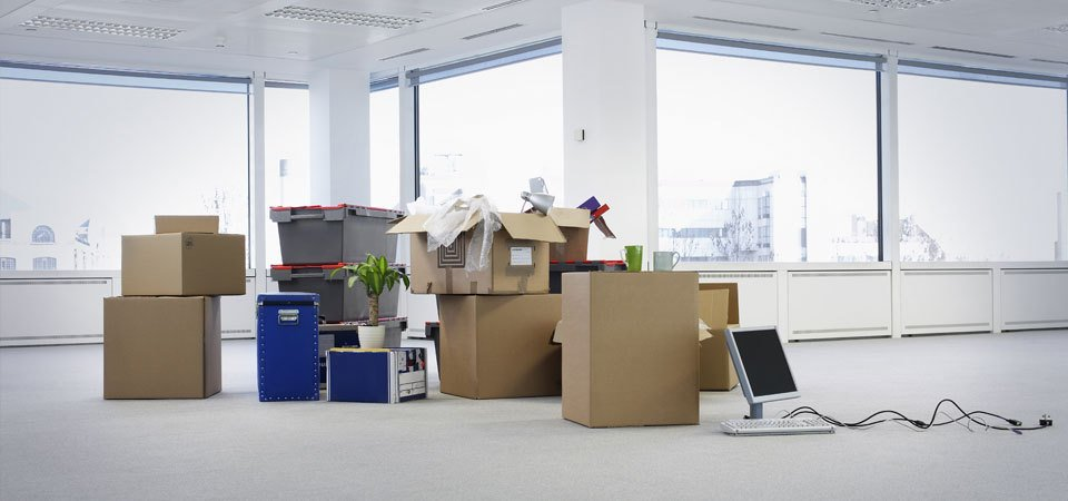 Packing boxes, computer screens and plants in the centre of an empty office