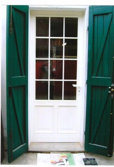 una porta d'entrata in legno di color bianco con dei pannelli di vetro