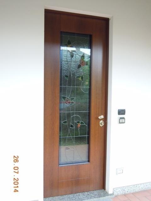 una porta con un pannello di vetro con dei disegni