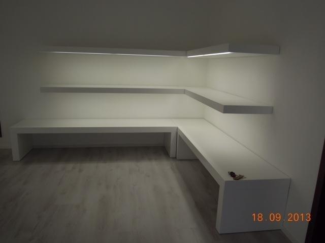 una stanza con pavimento in legno con delle panchine e delle mensole di color bianco