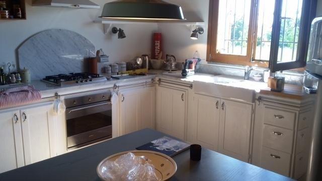 una cucina ad angolo in legno di color avorio