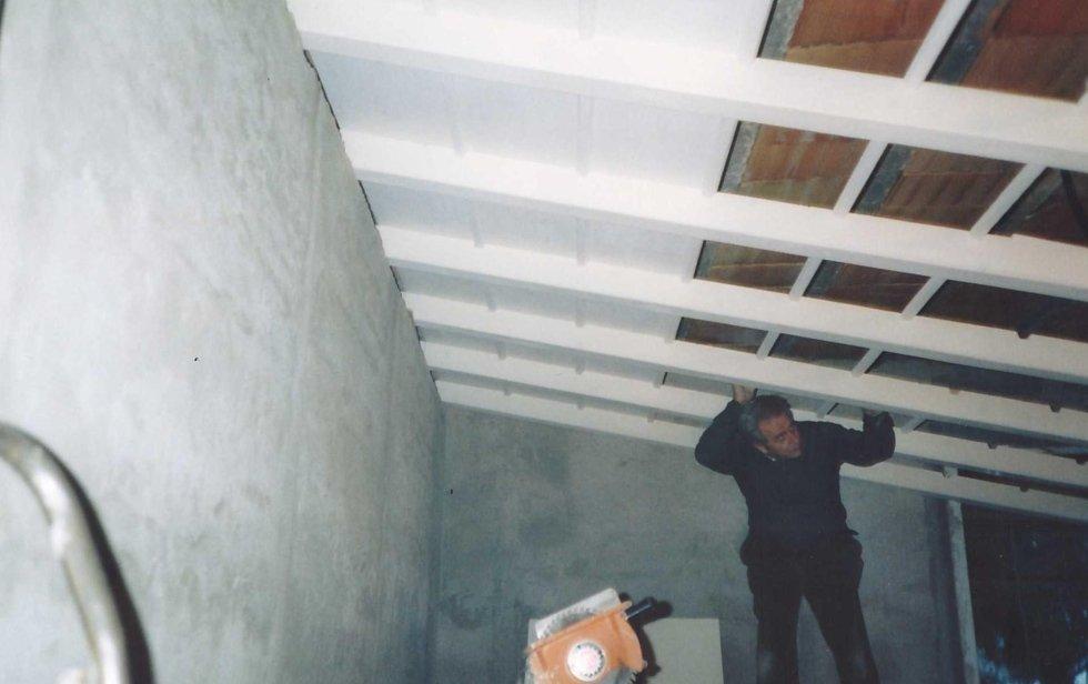 un operaio mentre monta delle assi di legno per un sottotetto